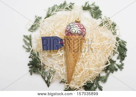 Colorful Christmas or New Year decoration with rose gold christmas ball ice cream cone blue tag with rose thread and tree branch on white background