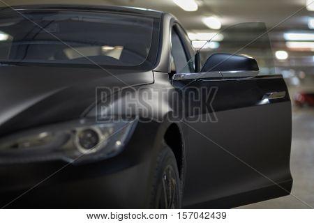 Modern black car with open door stands at underground parking, focus on mirror bracket.