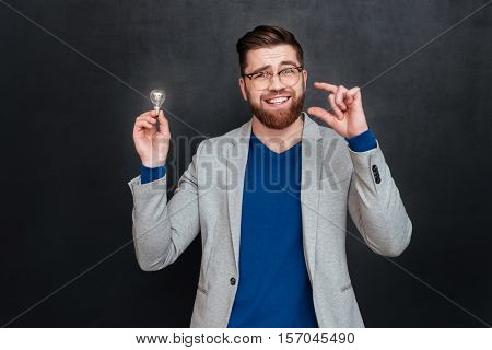 Cheerful bearded young businessman in glasses holding light bulb and showing small size over black backgorund