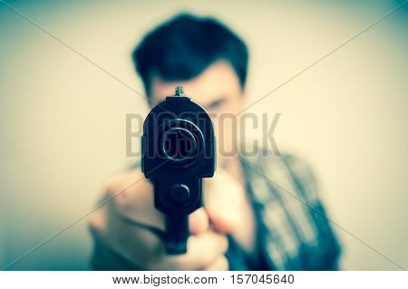 Crazy young man aiming automatic gun at you - retro style