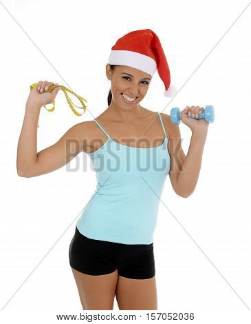 young beautiful and exotic hispanic woman in Christmas Santa hat holding weight and measure tape isolated on white background in healthy fitness and diet New Year resolution concept