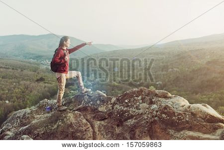 Explorer young woman with backpack standing on top of cliff on background of mountains and pointing into the distance outdoor