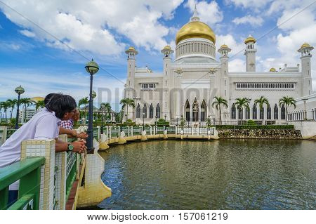 Bandar Seri Begawan,Brunei-Nov 12,2016:Tourists enjoying beautiful view of famous Sultan Omar Ali Saifuddien Mosque in Brunei Darusallam with blue sky background & reflection from the calm lake.
