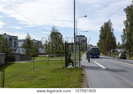 UMEA, SWEDEN ON AUGUST 30. View of a modern suburban settlement, street, traffic on August 30, 2016 in Umea, Sweden. Bus stop and lawns this side. Unidentified people. Editorial use.