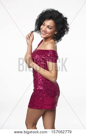 Holidays celebration concept. Happy playful young mixed race woman in fancy dress with sequins playing with her hair, looking to the side at blank copy space