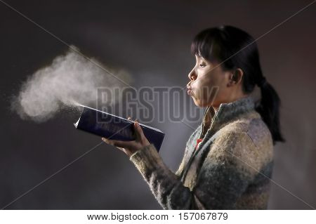 Asian woman blows dust off an old dictionary in this concept image.