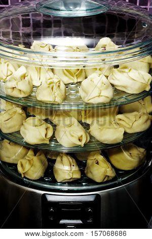 Healthy food in steamer, steam cooker with manti (steam dumplings)