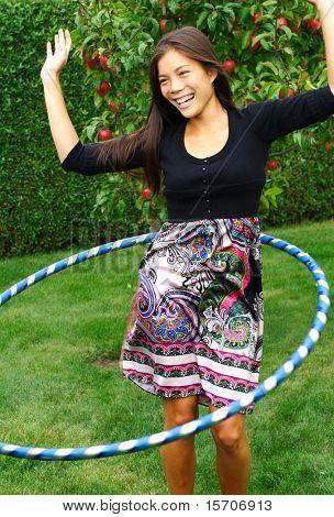 Hula hoop. Beautiful young woman doing hula hoop outdoors in the fall.