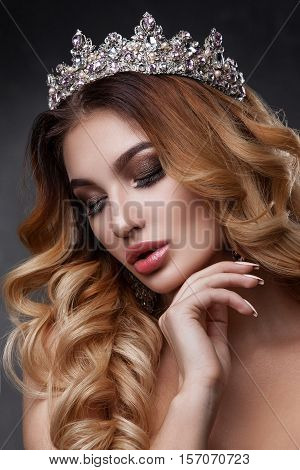 Beauty woman face with beautiful make-up colors. The image of the Queen. Dark hair a crown on his head clear skin beautiful face plump lips. Portrait shot in studio on a gray background.