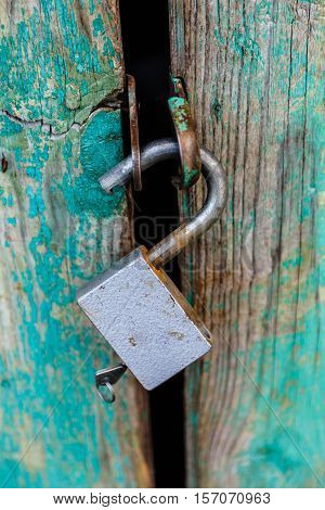Metal lock on an old wooden barn door.