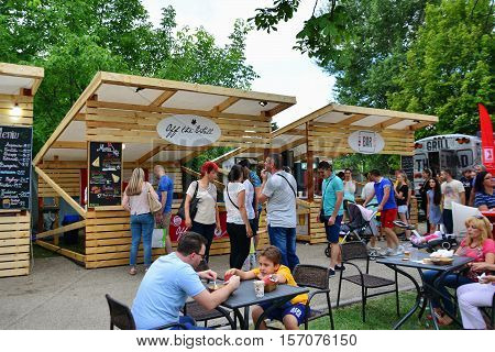 CLUJ-NAPOCA ROMANIA - JULY 9 2016: People have a snack in central park Cluj. Vendors in stalls sell tasty fast food from different cultures.
