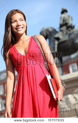 Madrid. Woman tourist sightseeing on Plaza Mayor Madrid, Spain. Beautiful woman in red dress. Tourist attraction, statue of Felipe III is in the background.