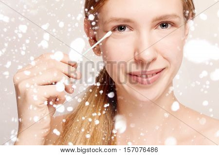 Woman removes makeup from the face with a cotton swab. Happy beautiful young woman cleaning skin by cotton swab. beauty people advertisement winter and health concept . over snow background