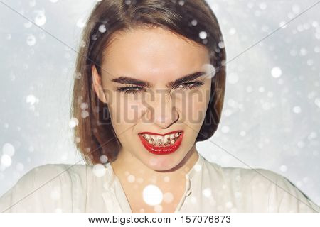 Young woman portrait with dental braces natural. beauty people advertisement winter and health concept . over snow background