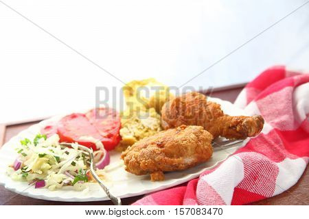 Fried chicken pieces with cornbread coleslaw and tomato slices with a bright background
