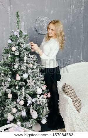 Young woman decorating christmas tree.Young woman during preparations for Christmas at home. Christmas atmosphere. Christmas decor.