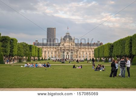 PARIS FRANCE June 18: Parisians and guests of the city rest on the lawn of the Champs de Mars on 18 June 2012. In the background is the building of the Paris Military school.