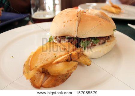 Hamburguesa de chorizo con papas gourmet en plato blanco