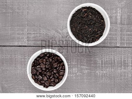 Coffee beans and loose tea in white bowls on wooden background