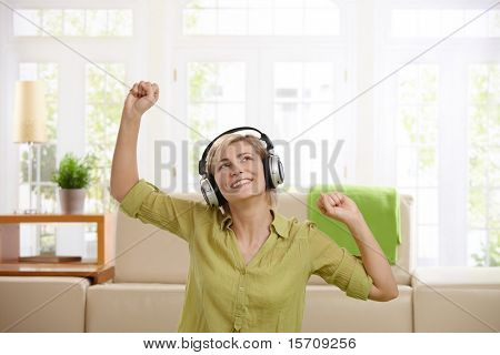 Woman having fun, enjoying music via headphones sitting at home with arms raised.?