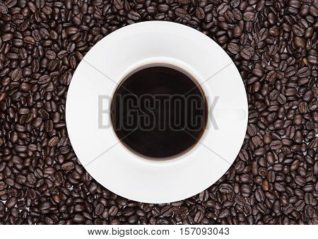 Cup of black coffee for breakfast with beans on coffee beans background