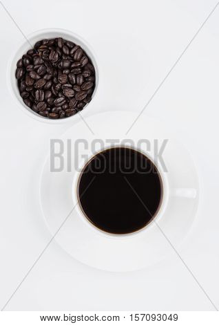 Cup of black coffee for breakfast with beans on white background