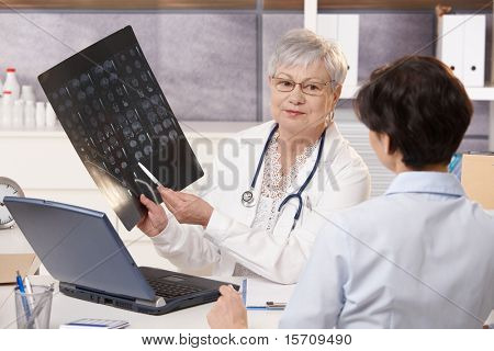 Senior doctor showing x-ray results to patient in office.?