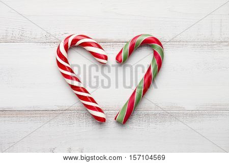 Peppermint candy cane heart on white wooden background