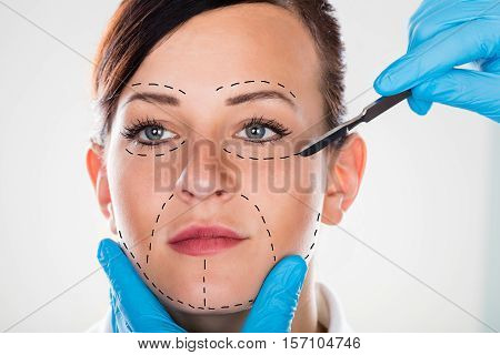 Close-up Of A Cosmetic Surgery With Scalpel On Young Woman