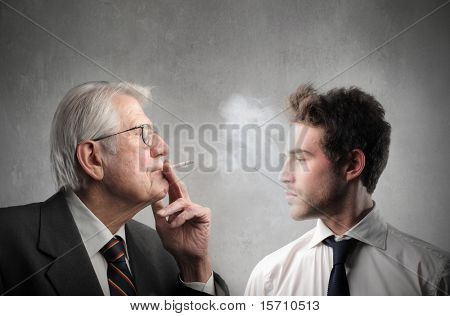 Senior businessman smoking in front of a younger one