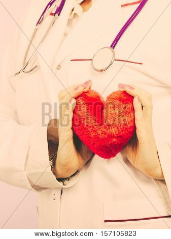 Love from working and helping people. Part body female doctor in white medical apron with heart. Enjoy work concept. Filtered.