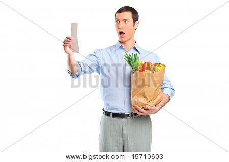 Shocked man looking at store receipt and holding a grocery bag isolated on white background