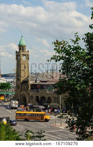 HAMBURG GERMANY - JULY 18 2016: a Beautiful view of famous Landungsbruecken with commercial harbor and Elbe river with blue sky and clouds in summer St. Pauli district Hamburg Germany