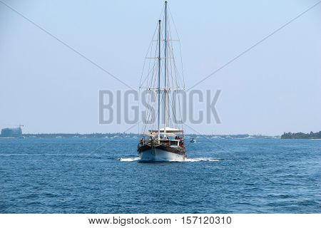 A nautical landscape with retro sailboat. Sea voyage on sailing yacht - luxury lifestyle in summer. Seashore with sailing vessel near islands soft light effect.