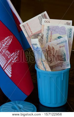 Cambodian riel and flag in a garbage bin.