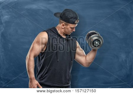 Portrait of a young handsome man in a black outfit standing and holding a silver dumbbell in his hand showing his muscled biceps during training on the dark blue background. Sport and healthy lifestyle. Keep fit. Athletic body. Exercises and warming up.