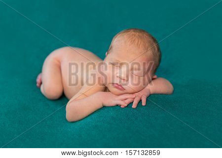 sweet naked newborn sleeping on stomach and hands with headband on dark turquoise blanket