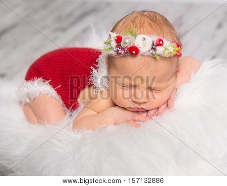 lovely newborn girl in red romper and colorful headband sleeping on white fluffy blanket