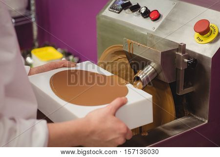 Mid section of worker filling mould with melted chocolate in kitchen