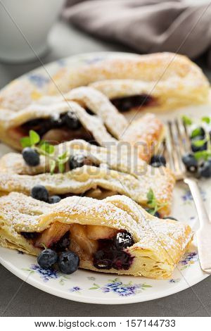 Puff pastry with apple and blueberry decorated with powdered sugar
