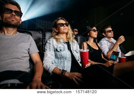 Group of people in 3D glasses watching movie in cinema. Men and women with drinks watching 3d film.