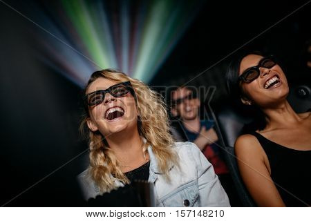 Smiling female friends watching 3d movie in theater. Happy young women watching 3d film in multiplex cinema.