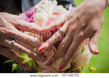 The groom and the bride stick to a hand over a wedding bouquet. Wedding bouquet and hands of couple.