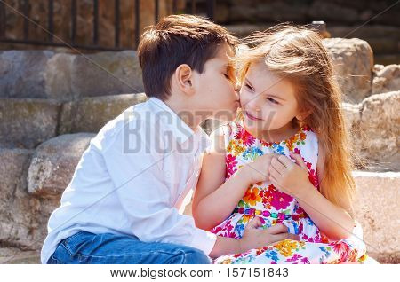 Children show love and affection to each other. Brother sister kissing. The boy courting a girl.