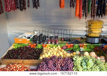 Fruits, berries cones, hot corn and Oriental sweets on the market