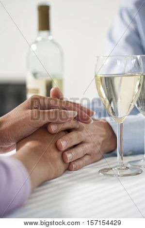 Female holding her hand over male hand at Valentine s day with a glasses of white wine. Soft close up