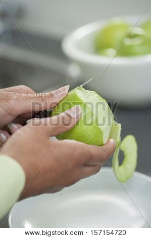 Female hands peeling skin off of a green apple using a paring knife