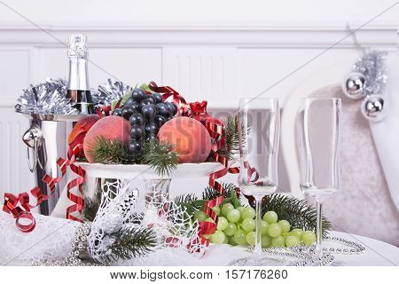Bottle of champagne in a bucket of fruit in a vase on the holiday table.