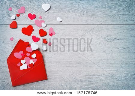 Valentines Day. Red envelope with heap of small hearts on wooden background. Copy space for your text