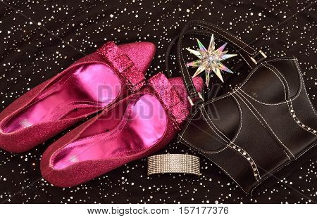 Fashion woman accessories. Glittery shoes, black handbag clutch. Essentials top view. isolated. Black background with sparkles. Beautifully organized. trendy. party.Holliday season,